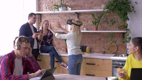 A tecnologia moderna no escritório, fêmea nova com o capacete da realidade virtual joga jogos quando os colaboradores comerem e c