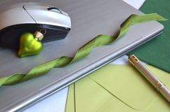 Tecnologia no trabalho durante o Natal Laptop fechado com rato, pena, cartões de nota e a decoração verde da bola do Natal fotografia de stock