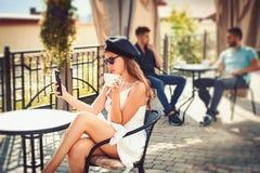 Tecnologia nuova E La donna gode di di bere il caffè espresso o il cappuccino adorable fotografia stock