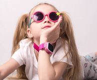 Tecnologia per i bambini: una ragazza che indossa i vetri rosa usa uno smartwatch fotografie stock
