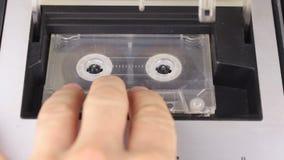 Tecnologia retro A pessoa para e ejeta a cassete áudio do gravador filme