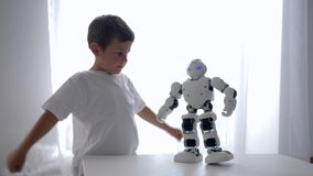 Tecnologia robot, giochi adorabili del bambino con i giocattoli moderni con intelligenza artificiale nella stanza luminosa video d archivio
