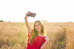 Tecnologia, vacanze estive, vacanza e concetto della gente - giovane donna sorridente in vestito rosso che prende selfie dallo sm Fotografie Stock