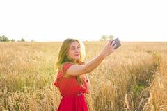 Tecnologia, vacanze estive, vacanza e concetto della gente - giovane donna sorridente in vestito rosso che prende selfie dallo sm Fotografia Stock