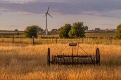 Tecnologia velha e nova O ancinho e a turbina eólica de feno em um Staffordshire colocam imagens de stock