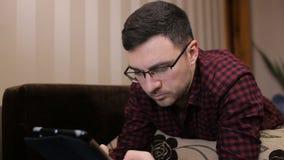 Tecnologia, visão e conceito dos povos - homem com o PC da tabuleta cansado dos monóculos em casa video estoque