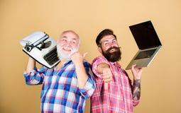 Tecnologias de Digitas Batalha das tecnologias Gera??o velha Os homens trabalham escrevendo dispositivos Vida moderna e restos do imagens de stock
