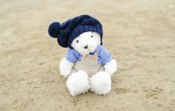 Teddie's bear cub sits on sand Stock Photography