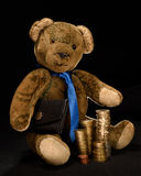 Teddy as a businessman with money or coins. Teddy as a businessman, who proudly presents its stacked money. He has a black briefcase under his arm and stacked Stock Photos