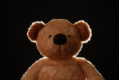 Teddy Bear. Back lit teddy bear against black background stock photo