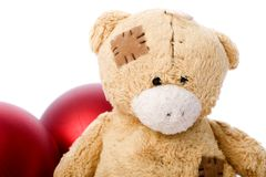 Teddy bear. A little teddy bear with red christmas balls Stock Photos