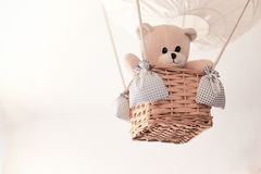 Teddy bear in a aerostatic balloon toy hanging from the ceiling. Stock Images
