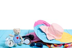 Teddy bear with alarm clock and summer accessories on blue wood. Stock Image
