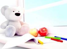 Teddy bear, apples, album, pencils on the windowsill. Royalty Free Stock Photography