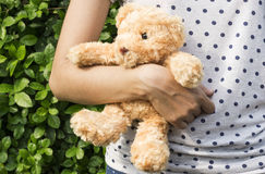 Teddy bear in the arm of a young woman. At park Royalty Free Stock Images