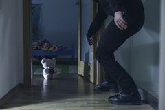 Teddy bear as a guardian can't do much. Shot of a burglar opening a door to a children's room with teddy bear on a floor Stock Images