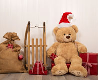 Teddy bear as a santa with an old wooden sleigh and red christma Royalty Free Stock Photo