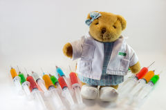 Teddy bear as a woman doctor with plastic medical syringes containing multicolor solutions and white background.`Medical concept`. Teddy bear is a soft toy in Stock Images