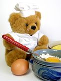 Teddy bear is baking. A cake. I don't know what sort. He should remove the flour on his face royalty free stock photos