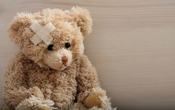Teddy bear with bandage on a wooden floor royalty free stock photography