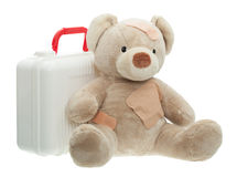 Teddy Bear with Bandages and Child Medical Kit. Teddy Bear with Bandages siting next to a Child medical kit to play doctor, closed plastic case.   Isolated Royalty Free Stock Photography