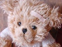 Teddy bear with bandaid. Unhappy teddy bear with bandaid on forehead stock photo