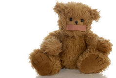 Teddy bear with bandaid on mouth. Stuffed teddy bear with bandaid on mouth Stock Photo