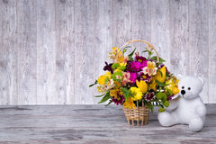 Teddy bear with a basket of spring flowers. Basket of spring flowers.Teddy bear with a basket of spring flowers stock image