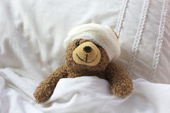 Teddy in bear bed with bandage on head Stock Photo