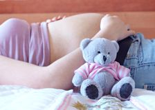 Teddy bear and Belly. Pregnant woman with a teddy bear Royalty Free Stock Photo