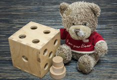 Teddy bear, big dice on old wood table.  Royalty Free Stock Photo