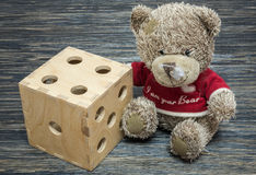 Teddy bear, big dice on old wood table.  Stock Images