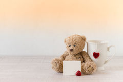 Teddy bear with a big white cup of tea and a red heart Royalty Free Stock Photography