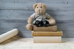 Teddy bear with binoculars sitting on the stack of old books Stock Photo