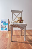 Teddy bear and blanket on chair with poster. Teddy bear, white blanket on white wooden chair with sign poster chill bliss calm relax royalty free stock photography