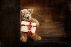 Teddy bear brings a Christmas present decorated with a red ball chain, dark rustic wooden background with copy space Royalty Free Stock Photography