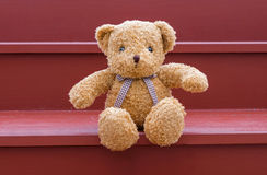 TEDDY BEAR brown color sitting on red staircase Royalty Free Stock Photo
