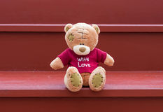 TEDDY BEAR brown color wear red shirt with love sitting on red s Stock Image