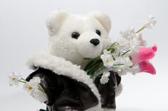 Teddy bear with a bunch of flowers. White teddy bear with a bunch of flowers stock photo