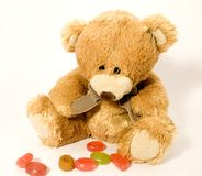 Teddy bear with candies. A sweet teddy bear looking at the candies arranged unsorted in front of him Stock Image