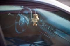 Teddy bear in the car, soft toy hanging on the rearview mirror royalty free stock photos