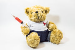 Teddy bear carrying a plastic medical syringe containing red liquid Royalty Free Stock Photo