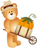 Teddy bear carrying pumpkin in wooden cart Royalty Free Stock Images