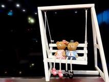Teddy Bear che si siede su un'oscillazione bianca Fotografia Stock