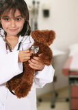Teddy Bear Check Up. A yong girl playing doctor with her teddy bear Stock Images