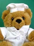 Teddy bear is the chef, green background. Teddy bear is wearing a chef's dressing. Does he knows how to cook or is he just pretending royalty free stock images