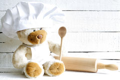 Teddy bear in chef hat with spoon abstract food background Royalty Free Stock Photos