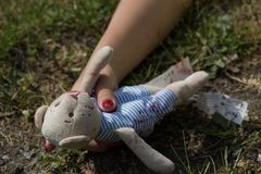 Teddy bear in the child hand after the accident. stock photo