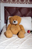 Teddy bear on  classic furniture bed with pillows Stock Images