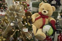 Teddy Bear com um laço vermelho que senta-se ao lado de uma árvore de Natal C fotos de stock